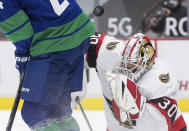 Ottawa Senators goalie Matt Murray (30) makes a blocker save while being screened by Vancouver Canucks' Jimmy Vesey during the second period of an NHL hockey game in Vancouver, British Columbia, Thursday, April 22, 2021. (Darryl Dyck/The Canadian Press via AP)