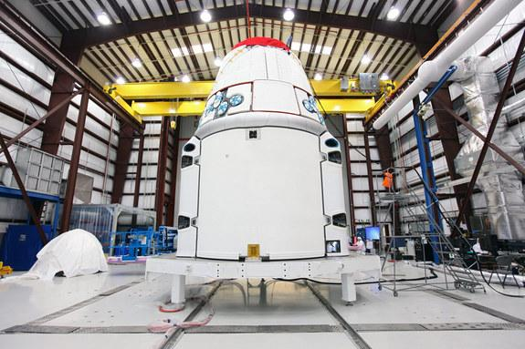 The Space Exploration Technologies, or SpaceX, Dragon spacecraft with solar array fairings attached, stands inside a processing hangar at Cape Canaveral Air Force Station, Fla. The spacecraft will launch on the upcoming SpaceX CRS-2 mission. I