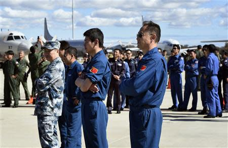 Air crew members from China, Malaysia and Japan involved in the search for missing Malaysia Airlines plane MH370, wait for an official photograph as they stand on the tarmac at the RAAF Pearce Base in Bullsbrook