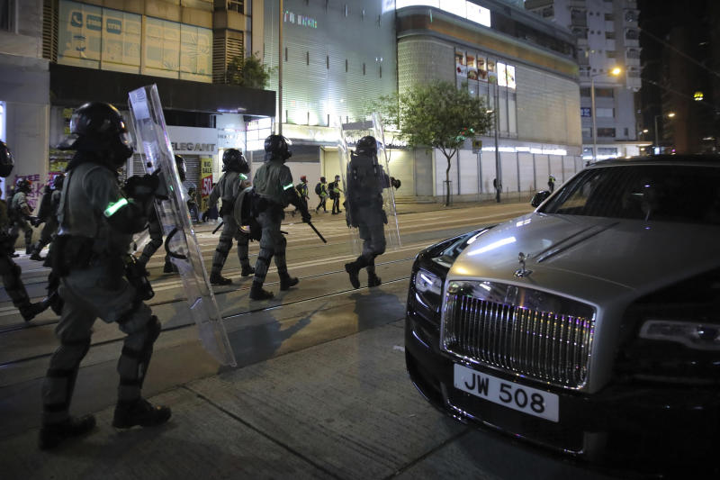 Police officers in riot gear move past a parked Rolls Royce automobile during a protest in Hong Kong, Saturday, Nov. 2, 2019. Pro-democracy protesters attacked the office of Chinese news agency Xinhua for the first time Saturday, after familiar chaos downtown that saw police and demonstrators trading petrol bombs, tear gas and water cannon in the 22nd straight weekend of unrest. (AP Photo/Kin Cheung)