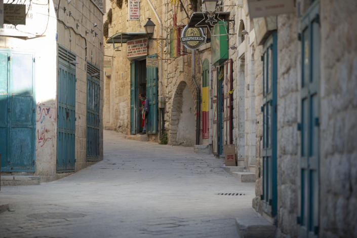 A Palestinian vendor stands in front of his shop near the Church of the Nativity, traditionally believed to be the birthplace of Jesus Christ, in the West Bank City of Bethlehem, Monday, Nov. 23, 2020. Normally packed with tourists from around the world at this time of year, Bethlehem resembles a ghost town – with hotels, restaurants and souvenir shops shuttered by the pandemic. (AP Photo/Majdi Mohammed)