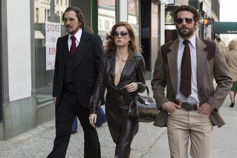 "This photo released by Sony Pictures shows Christian Bale, left, as Irving Rosenfeld, Amy Adams as Sydney Prosser, and Bradley Cooper as Richie Dimaso walking down Lexington Avenue in a scene from Columbia Pictures' film, ""American Hustle."" (AP Photo/Sony - Columbia Pictures, François Duhamel)"
