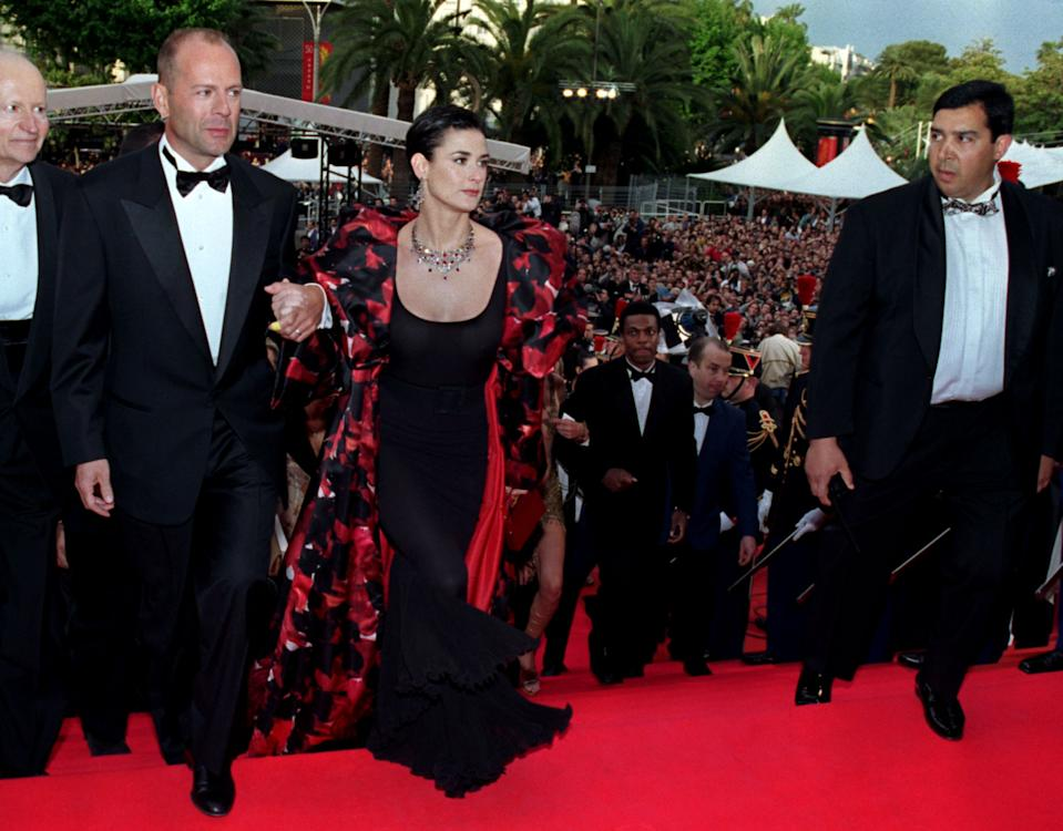 """U.S. actor Bruce Willis (L) arrives with his wife Demi Moore (2nd L) under the watchful eyes of a body guard for the screening of French director Luc-Besson's """"Le Cinquieme Element"""" at the opening of the 50th Cannes Film Festival, May 7. Willis stars in the futuristic film that is screened out of competition."""