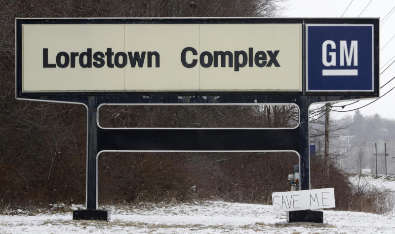 """FILE - In this March 6, 2019 file photo, A """"Save Me"""" sign rests against the Lordstown Complex sign in Lordstown, Ohio.  The long-struggling Rust Belt community of Youngstown, Ohio, which was stung by the loss of the massive General Motors Lordstown plant this year, wants to become a research and production hub for electric vehicles.. But Youngstown faces competition from places like Detroit and China that are taking big roles in developing electric vehicles. (AP Photo/Tony Dejak, File)"""