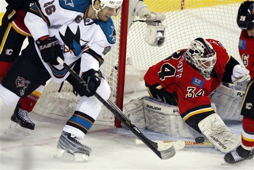 San Jose Sharks' Michal Handzus, left, of Slovakia, tries to get the puck past Calgary Flames goalie Miikka Kiprusoff, of Finland, during the second period of an NHL hockey game, Sunday, Jan. 20, 2013, in Calgary, Alberta. (AP Photo/The Canadian Press, Jeff McIntosh)