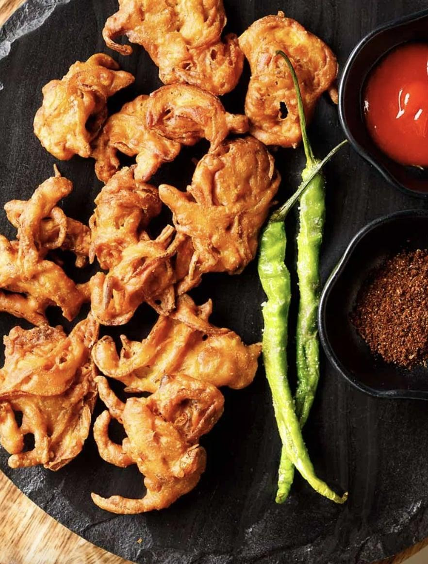 """<p>Craving this popular Indian street food? We've got you covered. Onion pakoda are basically onion fritters made with a different kind of flour (besan), and wow, are they good. You can either bake them in the oven or whip them up in an air fryer, meaning you can be chowing down on these in no time. </p> <p><strong>Get the recipe</strong>: <a href=""""https://www.vegrecipesofindia.com/onion-pakoras-making-onion-pakorasfritters/"""" class=""""link rapid-noclick-resp"""" rel=""""nofollow noopener"""" target=""""_blank"""" data-ylk=""""slk:classic onion pakoda"""">classic onion pakoda</a></p>"""