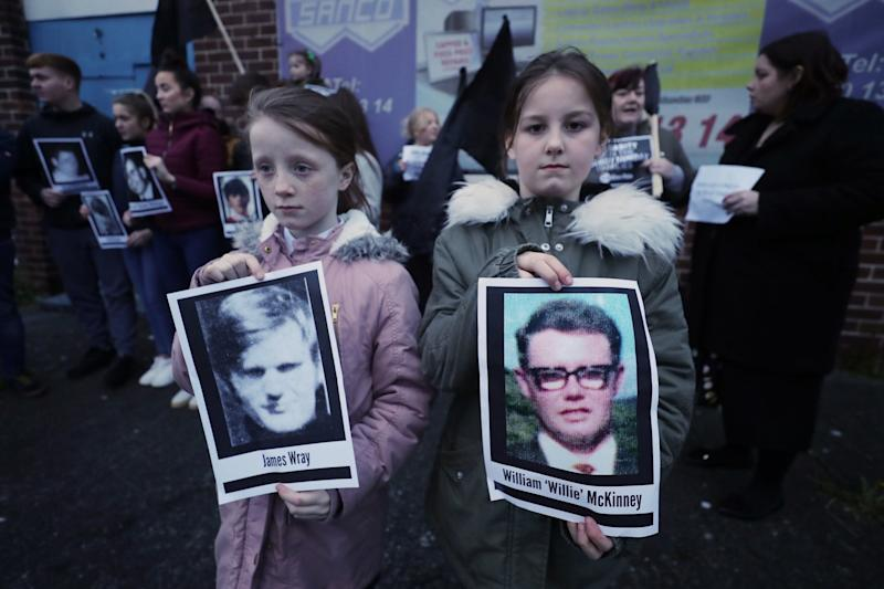 Two children hold pictures of Bloody Sunday victims James Wray and William McKinney (PA)