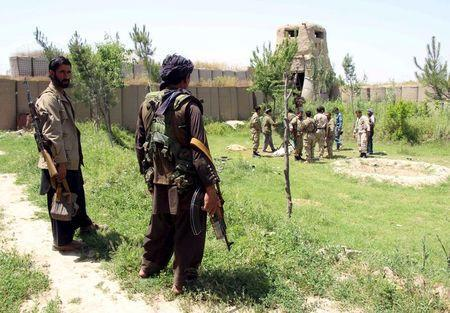 Afghan militias and policemen gather as they discuss during a battle at the Chardara district of Kunduz province, May 3, 2015. REUTERS/Stringer