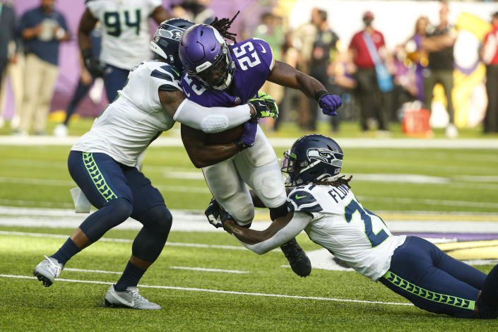 Minnesota Vikings running back Alexander Mattison (25) is tackled by Seattle Seahawks strong safety Quandre Diggs (6) and cornerback Tre Flowers (21) in the first half of an NFL football game in Minneapolis, Sunday, Sept. 26, 2021. (AP Photo/Bruce Kluckhohn)