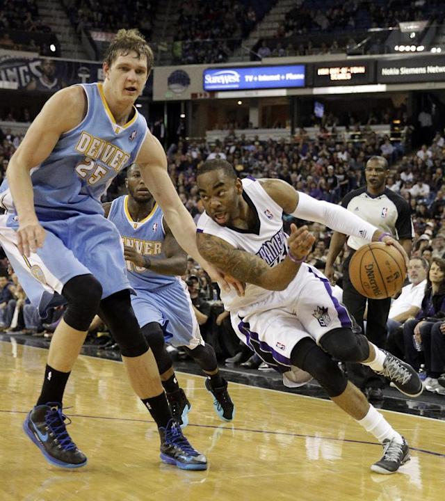 Sacramento Kings guard Marcus Thornton, right, drives against Denver Nuggets center Timofey Mozgov, of Russia, during the fourth quarter of an NBA basketball game in Sacramento, Calif., Sunday, Jan. 26, 2014. The Nuggets won 125-117.(AP Photo/Rich Pedroncelli)