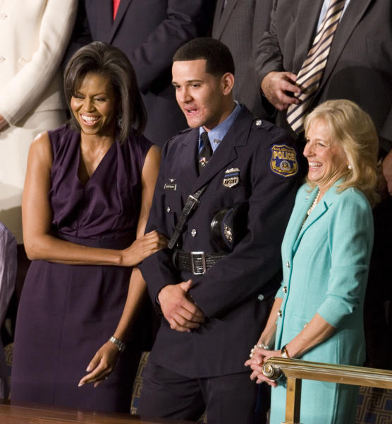 FILE - In this Tuesday, Feb. 24, 2009 file photo, first lady Michelle Obama and Jill Biden, wife of Vice President Joe Biden, stand with Philadelphia Police Officer Richard DeCoatsworth during President Barack Obama's address to a joint session of Congress in the House Chamber of the Capitol in Washington. The former Philadelphia police officer once hailed as a hero and given a seat next to the first lady at a speech by President Obama has been arrested and charged with rape and other crimes for an alleged Thursday, May 16, 2013 incident. (AP Photo/Evan Vucci)