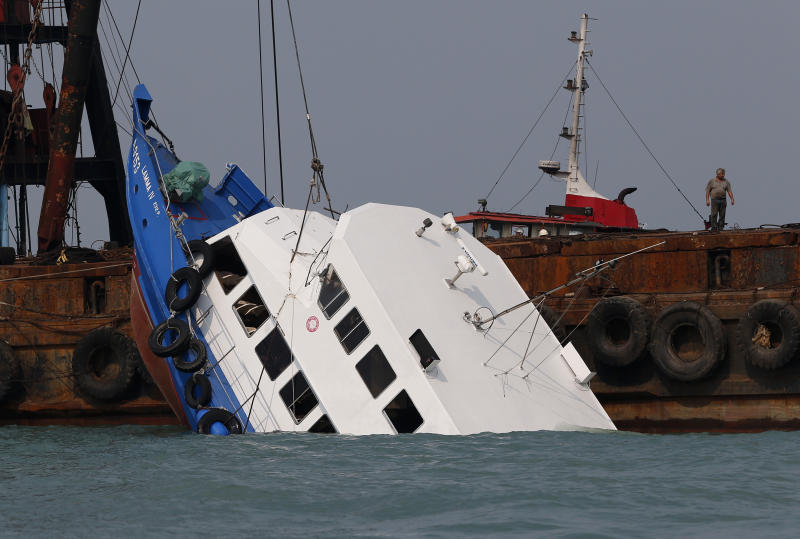 Officials check on a half submerged boat after it collided Monday night near Lamma Island, off the southwestern coast of Hong Kong Island Tuesday Oct. 2, 2012. The boat packed with revelers on a long holiday weekend collided with a ferry and sank off Hong Kong, killing at least 36 people and injuring dozens, authorities said. (AP Photo/Vincent Yu)
