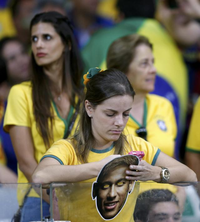 A fan holds a mask of Brazil's Neymar during the 2014 World Cup semi-finals between Brazil and Germany at the Mineirao stadium in Belo Horizonte July 8, 2014. REUTERS/Marcos Brindicci (BRAZIL - Tags: TPX IMAGES OF THE DAY SOCCER SPORT WORLD CUP)