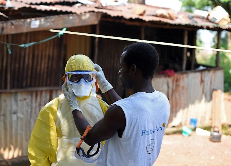 A health workers from the Sierra Leone's Red Cross Society Burial Team 7 prepares to remove a corpse from a house in Freetown on November 12, 2014 (AFP Photo/Francisco Leong)