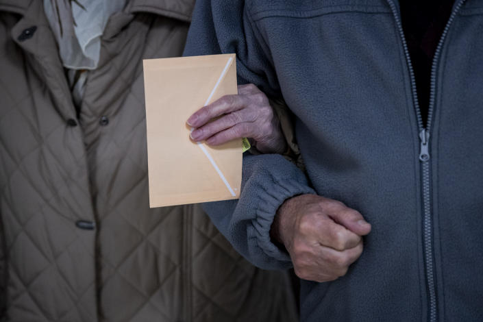 An elderly couple walk into a polling station during the regional election in Madrid, Spain, Tuesday, May 4, 2021. Over 5 million Madrid residents are voting for a new regional assembly in an election that tests the depths of resistance to lockdown measures and the divide between left and right-wing parties. (AP Photo/Bernat Armangue)