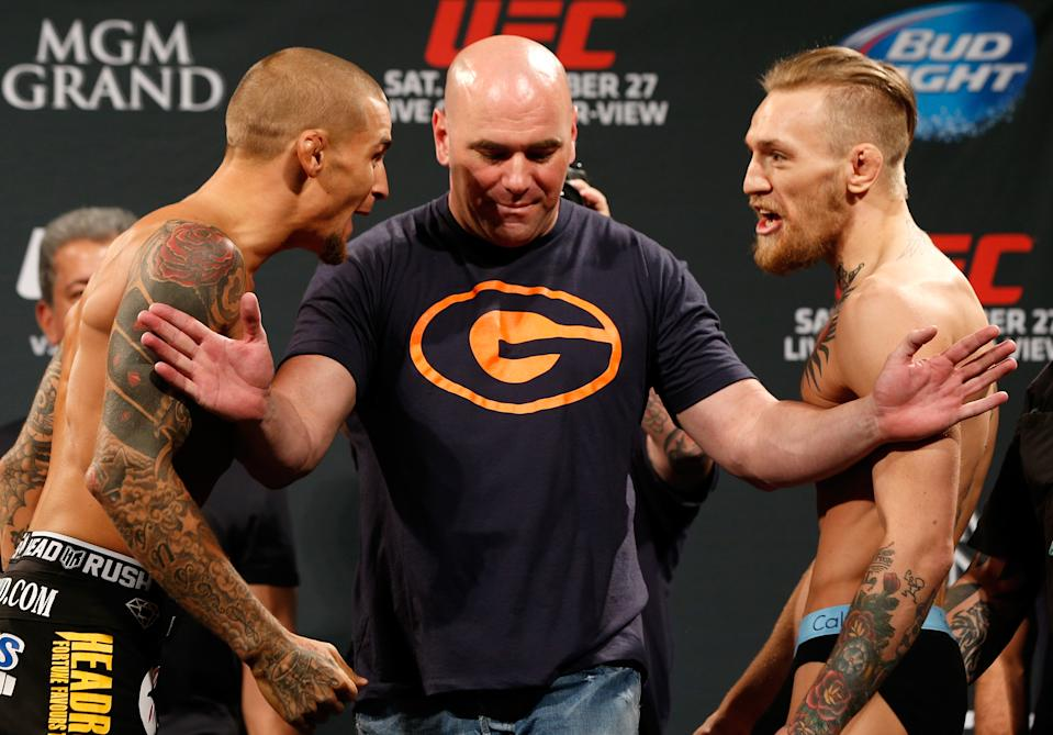 Dustin Poirier and Conor McGregor yell at each other with Dana White in between holding them apart.