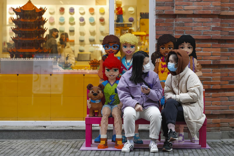 In this photo released by Xinhua News Agency, women wearing protective masks to prevent the new coronavirus outbreak chat with each other outside a Lego store at a re-opened commercial street in Wuhan in central China's Hubei province on Monday, March 30, 2020. Shopkeepers in the city at the center of China's virus outbreak were reopening Monday but customers were scarce after authorities lifted more of the anti-virus controls that kept tens of millions of people at home for two months. (Shen Bohan/Xinhua via AP)