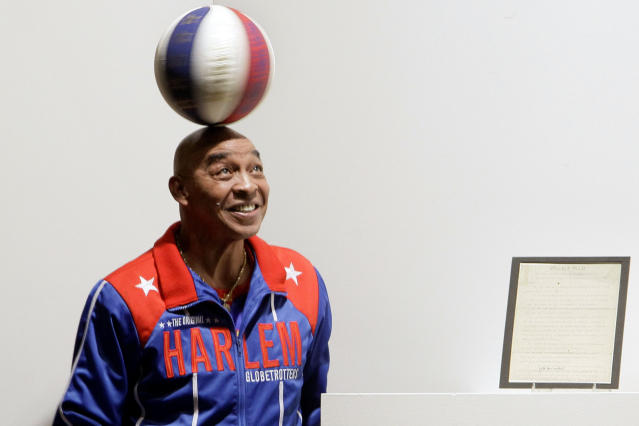 """FILE - In this Dec. 10, 2010, file photo, Harlem Globetrotters Fred """"Curly"""" Neal spins a ball on his head prior to the bidding for the Naismith Rules, the original rules for basketball, framed at right, at Sotheby's in New York. Neal, the dribbling wizard who entertained millions with the Harlem Globetrotters for parts of three decades, has died the Globetrotters announced Thursday, March 26, 2020. He was 77. Neal played for the Globetrotters from 1963-85, appearing in more than 6,000 games in 97 countries for the exhibition team known for its combination of comedy and athleticism. (AP Photo/Richard Drew, File)"""