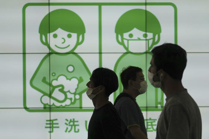 Image: People wearing face masks to help curb the spread of the coronavirus walk in front of a banner reminding the public washing hands, Thursday, July 16, 2020, in Tokyo. (Eugene Hoshiko / AP)