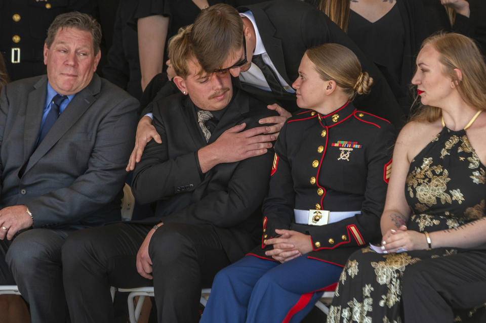 Marine Sgt. Nicole Gee's husband, Jarod Gee, second left, is comforted at her memorial at Bayside Church Adventure Campus in Roseville, Calif., Saturday, Sept. 18, 2021. Sgt. Gee lost her life, along with 12 other U.S. service members, in a bombing attack at the Kabul airport in Afghanistan on August 26. (Renee C. Byer/The Sacramento Bee via AP)