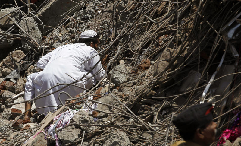 An Indian man looks for survivors in the debris of a building that collapsed on the outskirts of Mumbai, India, Friday, April 5, 2013. The half-finished building that was being constructed illegally in a suburb of India's financial capital collapsed on Thursday, killing 35 people and injuring more than 50 others, police said Friday. (AP Photo/Rajanish Kakade)