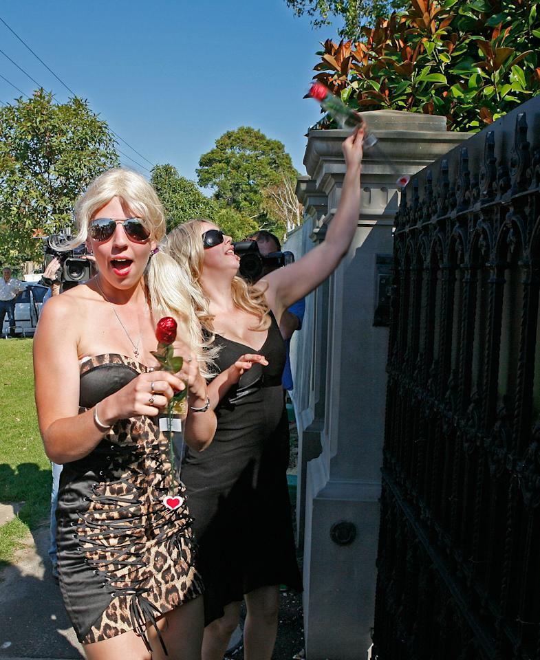 MELBOURNE, AUSTRALIA - FEBRUARY 14:  Promotional girls throw Valentine roses over the fence into the garden of former Australian cricketer Shane Warne, believed to be at home with actress Elizabeth Hurley on February 14, 2011 in Melbourne, Australia.  (Photo by Scott Barbour/FilmMagic)