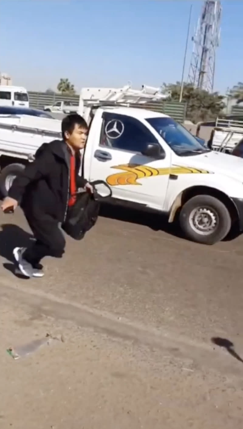 Pictured is a Chinese taxi passenger on a busy ring road next to a ute after he was dumped by his driver.