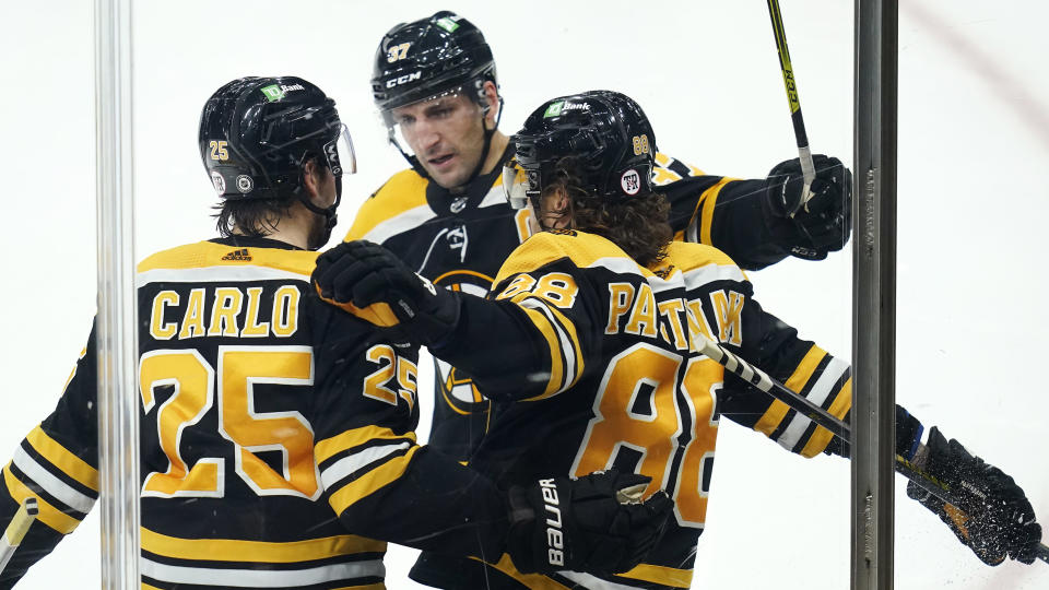 Boston Bruins right wing David Pastrnak (88) is congratulated by Brandon Carlo (25) and Patrice Bergeron, center, after his goal against the Washington Capitals during the third period of an NHL hockey game, Wednesday, March 3, 2021, in Boston. (AP Photo/Charles Krupa)
