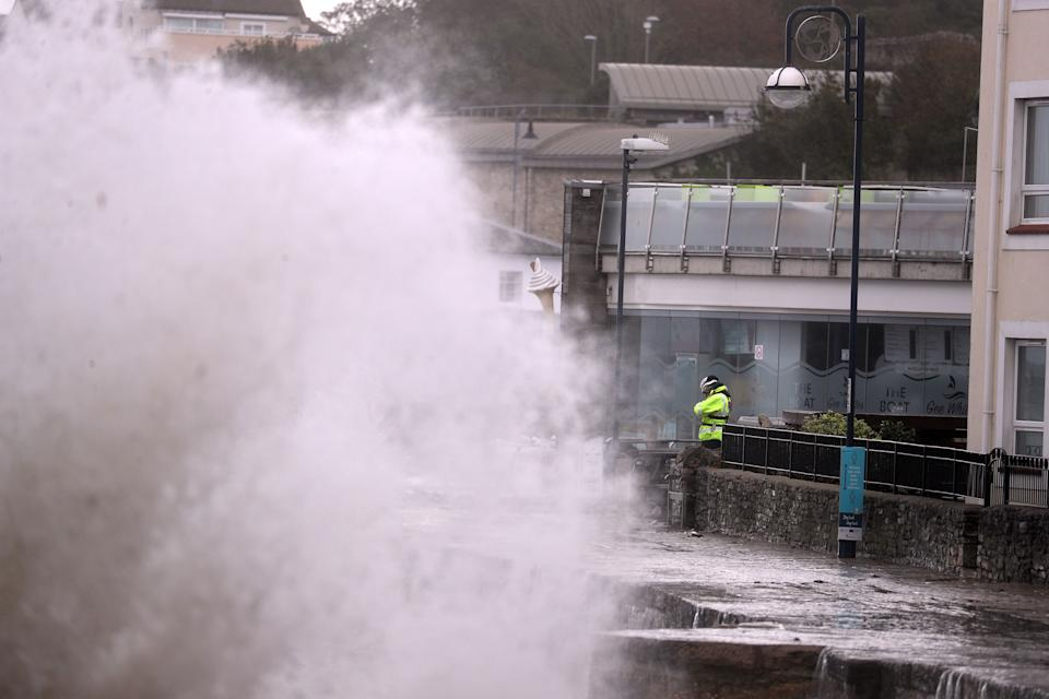 A member of the Coastguard watches as waves crash along the coast at Swanage in Dorset. Parts of the UK are preparing to be lashed by heavy rain and high winds as Storm Alex heralds the arrival of a stretch of bad weather over the weekend.