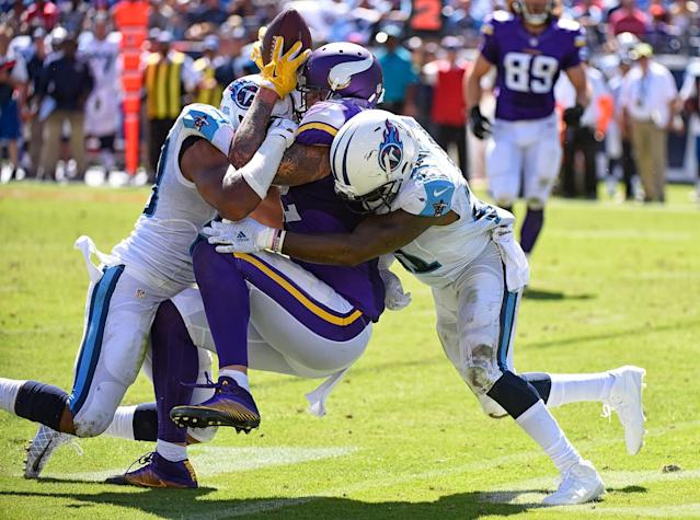 <p>Da'Norris Searcy #21 and Wesley Woodyard #59 of the Tennessee Titans sandwich tackle Kyle Rudolph #82 of the Minnesota Vikings, knocking the ball loose during the second half at Nissan Stadium on September 11, 2016 in Nashville, Tennessee. (Photo by Frederick Breedon/Getty Images) </p>
