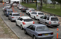 People queue at a drive through COVID-19 testing station at a beach in Sydney, Australia, Saturday, Dec. 19, 2020. Sydney's northern beaches will enter a lockdown similar to the one imposed during the start of the COVID-19 pandemic in March as a cluster of cases in the area increased to more than 40. (AP Photo/Mark Baker)