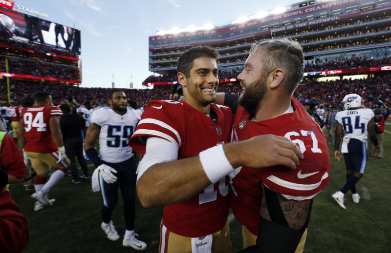 San Francisco 49ers quarterback Jimmy Garoppolo, center, hugs teammate Daniel Kilgore after a 25-23 win over the Titans. (AP)