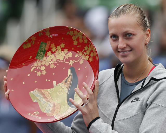 Petra Kvitova of the Czech Republic holds her winner's plate for photos during an award ceremony following her victory over Angelique Kerber of Germany at the final match of the Pan Pacific Open Tennis tournament in Tokyo, Saturday, Sept. 28, 2013. Kvitova won the tournament 6-2, 0-6, 6-3. (AP Photo/Koji Sasahara)