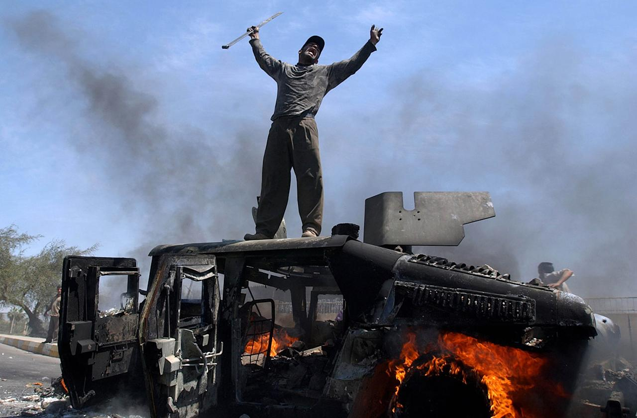 <p>An Iraqi man celebrates on top of a burning U.S. Army Humvee in the northern part of Baghdad, Iraq, April 26, 2004. (Photo: Muhammed Muheisen/AP) </p>