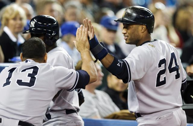 New York Yankees' Robinson Cano celebrates with Alex Rodriguez, left after scoring against the Toronto Blue Jays during the eighth inning of a baseball game in Toronto, Wednesday, Sept. 18, 2013. The Yankees won 4-3. (AP Photo/The Canadian Press, Mark Blinch)