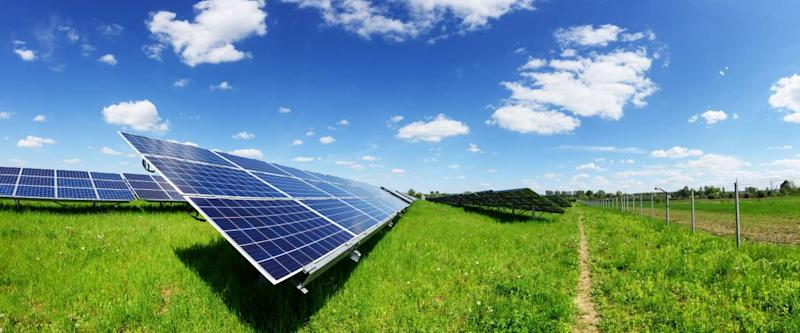 Solar panel on blue sky background. Green grass and cloudy sky.