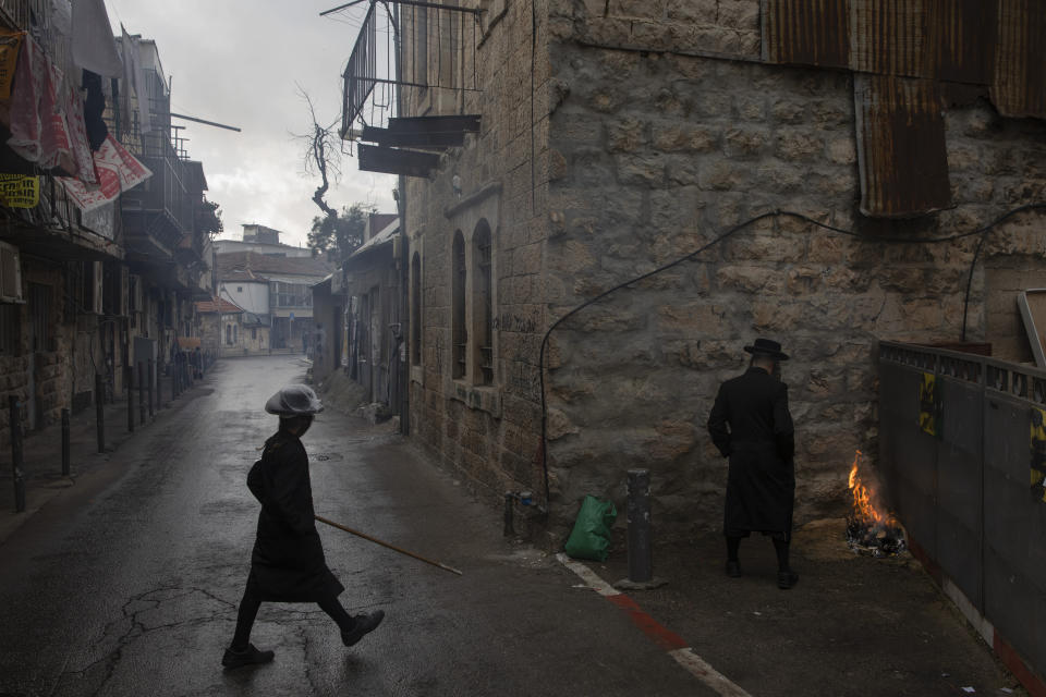 Ultra-Orthodox Jewish man burns leavened items in final preparation for the Passover holiday in Jerusalem, Friday, March 26, 2021. Israelis will once again hold large family gatherings this weekend to celebrate Passover, the festive Jewish holiday recalling the biblical flight of the Israelites from Egypt. That's thanks to a highly successful coronavirus vaccination campaign that has inoculated 80% of the country's adult population. (AP Photo/Oded Balilty)