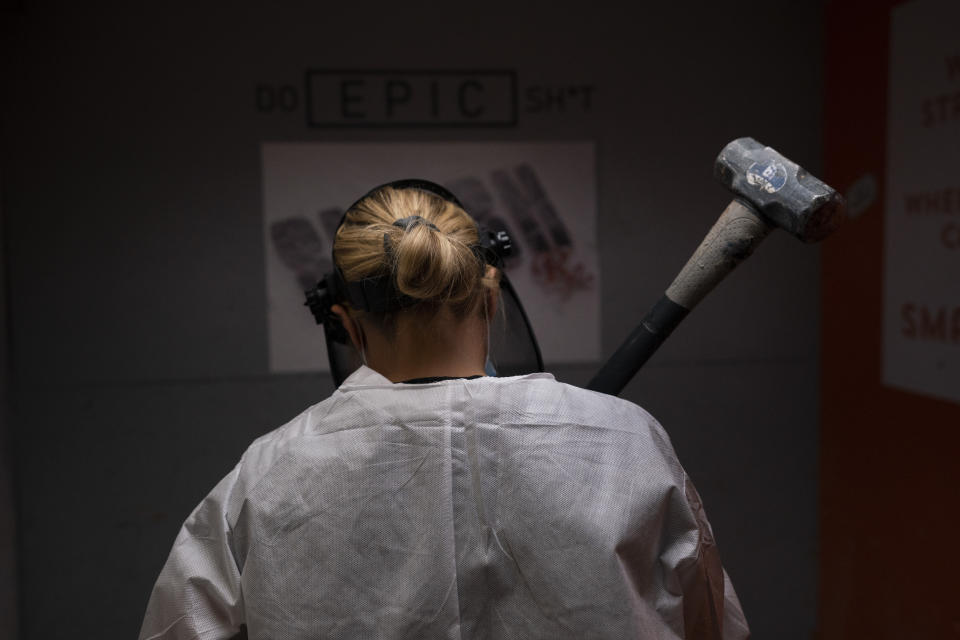 Michelle Elohim, a mother of four children, holds hammer to smash a side table in a rage room at Smash RX LLC Westlake Village, Calif., Friday, Feb. 5, 2021. (AP Photo/Jae C. Hong)