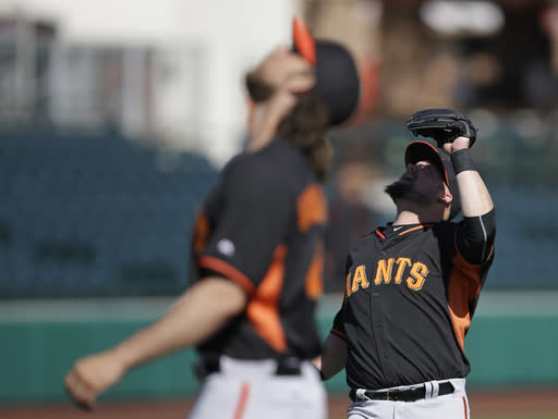 San Francisco Giants' Casey McGehee, right, watches a fly ball during spring training baseball practice Friday, Feb. 27, 2015, in Scottsdale, Ariz. Madison Bumgarner is at left. (AP Photo/Darron Cummings)