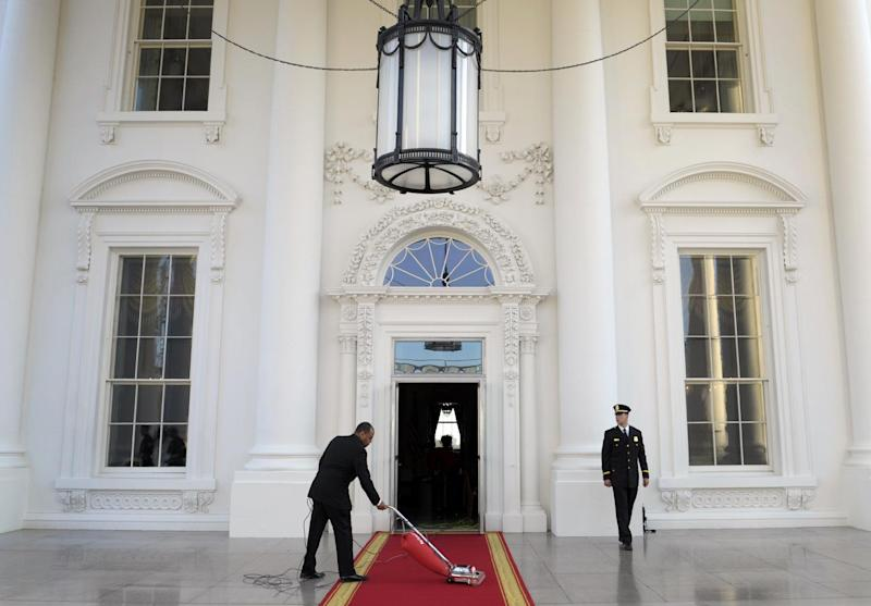 FILE - In this March 14, 2012, file photo, the red carpet of the North Portico is prepared for President Barack Obama and first lady Michelle Obama to welcome Britain's Prime Minister David Cameron and his wife Samantha to the White House for a State Dinner in Washington. Now in its second week, the partial government shutdown has taken its toll on the White House, where about 3 of 4 staffers have been furloughed, barred even from checking the Blackberries they usually clutch like worry beads. Of the 1,701 advisers, assistants, number-crunchers, butlers, chefs and landscapers who work at the White House on a normal day, fewer than 450 are on duty, according to Obama's budget office. (AP Photo/Susan Walsh, File)