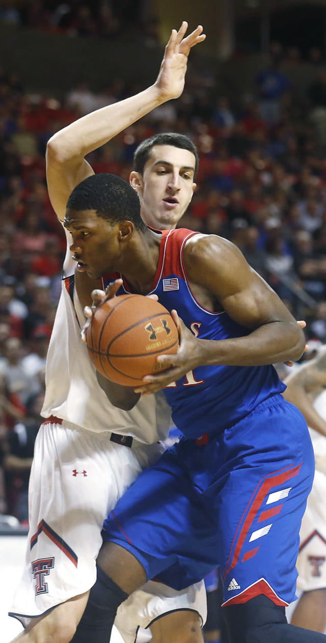 Texas Tech's Dejan Kravic defends Kansas' Joel Embiid, right during their NCAA college basketball game in Lubbock, Texas, Tuesday, Feb, 18, 2014. (AP Photo/Lubbock Avalanche-Journal, Stephen Spillman)