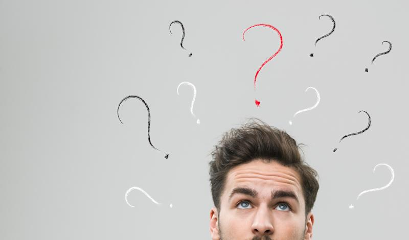 Man looking up and wondering in front of a wall with question marks.