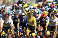Slovenia's Tadej Pogacar, wearing the overall leader's yellow jersey, waves as he rides with his UAE Team Emirates teammates as they lead the pack during the twenty-first and last stage of the Tour de France cycling race over 108.4 kilometers (67.4 miles) with start in Chatou and finish on the Champs Elysees in Paris, France,Sunday, July 18, 2021. (AP Photo/Christophe Ena)