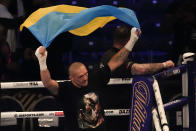 Oleksandr Usyk of Ukraine holds up the Ukrainian flag after his unanimous decision victory over Anthony Joshua of Britain in their WBA (Super), WBO and IBF boxing title bout at the Tottenham Hotspur Stadium in London, Saturday, Sept. 25, 2021. (AP Photo/Frank Augstein)