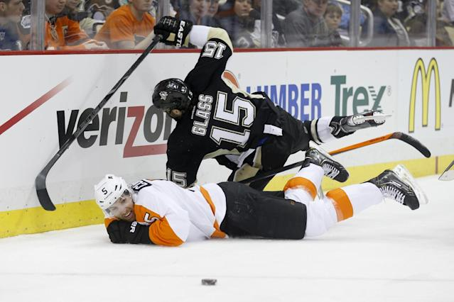 The pucks slides away as Pittsburgh Penguins' Tanner Glass (15) and Philadelphia Flyers' Braydon Coburn (5) slide into the boards during the second period of an NHL hockey game on Sunday, March 16, 2014, in Pittsburgh. (AP Photo/Keith Srakocic)