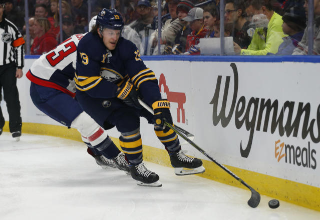 Buffalo Sabres defenseman Jake McCabe (19) carries the puck past Washington Capitals forward Tom Wilson (43) during the first period of an NHL hockey game, Saturday, Feb. 23, 2019, in Buffalo N.Y. (AP Photo/Jeffrey T. Barnes)