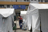 A health worker wearing a protective suit walks beside tents at a parking lot that has been converted into an extension of the Gat Andres Bonifacio Memorial Medical Center in Manila, Philippines on Monday, Aug. 3, 2020. Philippine President Rodrigo Duterte is reimposing a moderate lockdown in the capital and outlying provinces after medical groups appealed for the move as coronavirus infections surge alarmingly. (AP Photo/Aaron Favila)