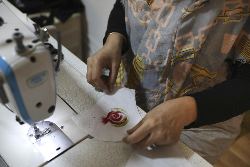 Elham Karami sews a protective face mask at a workshop of Bavar charity in Tehran, Iran, Monday, Nov. 23, 2020. As the coronavirus pandemic ravages Iran, a women's group hopes to empower its members by helping them make and sell face masks. (AP Photo/Vahid Salemi)