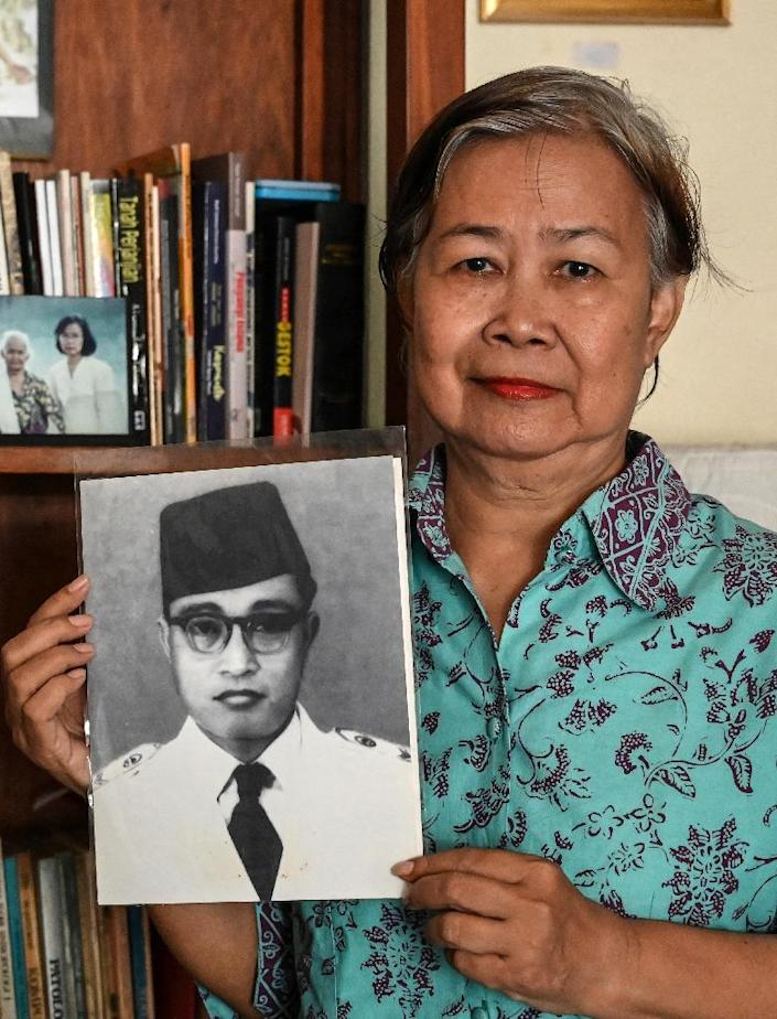 Uchikowati Fauzia, the daughter of a once-imprisoned communist Djohar Arifin Santosa, posing with her father's photograph in Jakarta. Upwards of half a million leftists were massacred across the Southeast Asian nation in the mid-Sixties (AFP Photo/BAY ISMOYO)