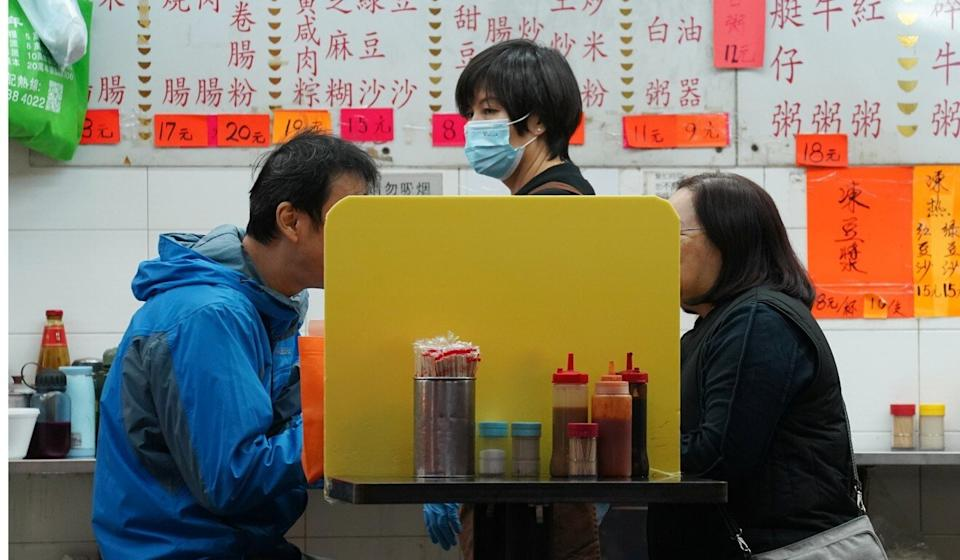 People dine at a table in a Hong Kong restaurant with a partition board installed to prevent the spread of Covid-19. Photo: Reuters